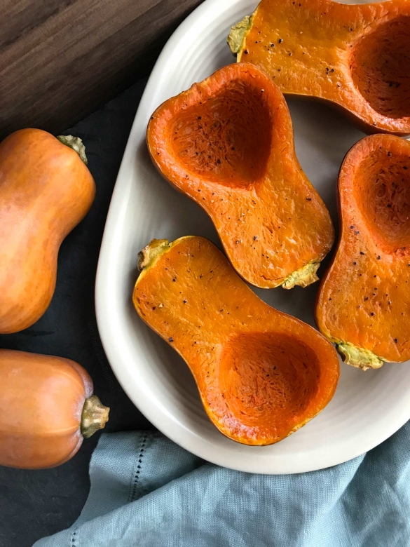 Halved, roasted honeynut squash (a seasonal winter squash variety).