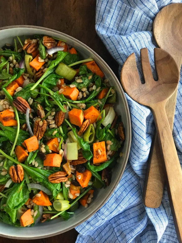 A salad with sweet potato, farro and arugula with coconut curry dressing.