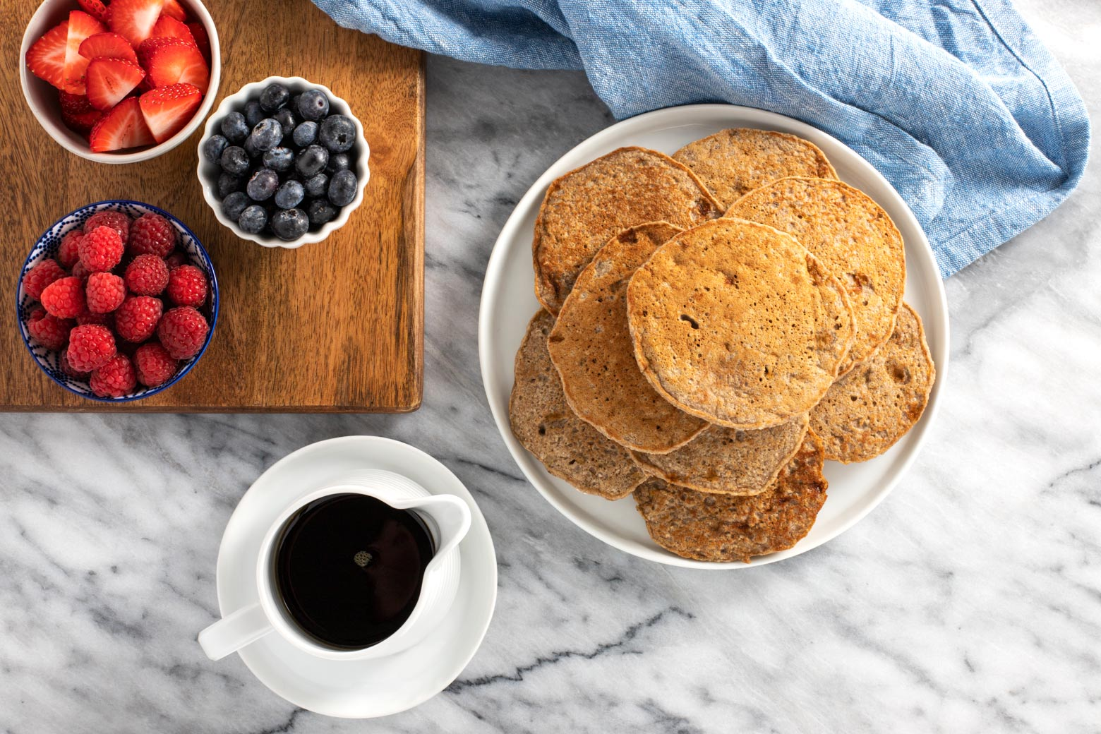 Stack of buckwheat banana pancakes with fresh berries and maple syrup.