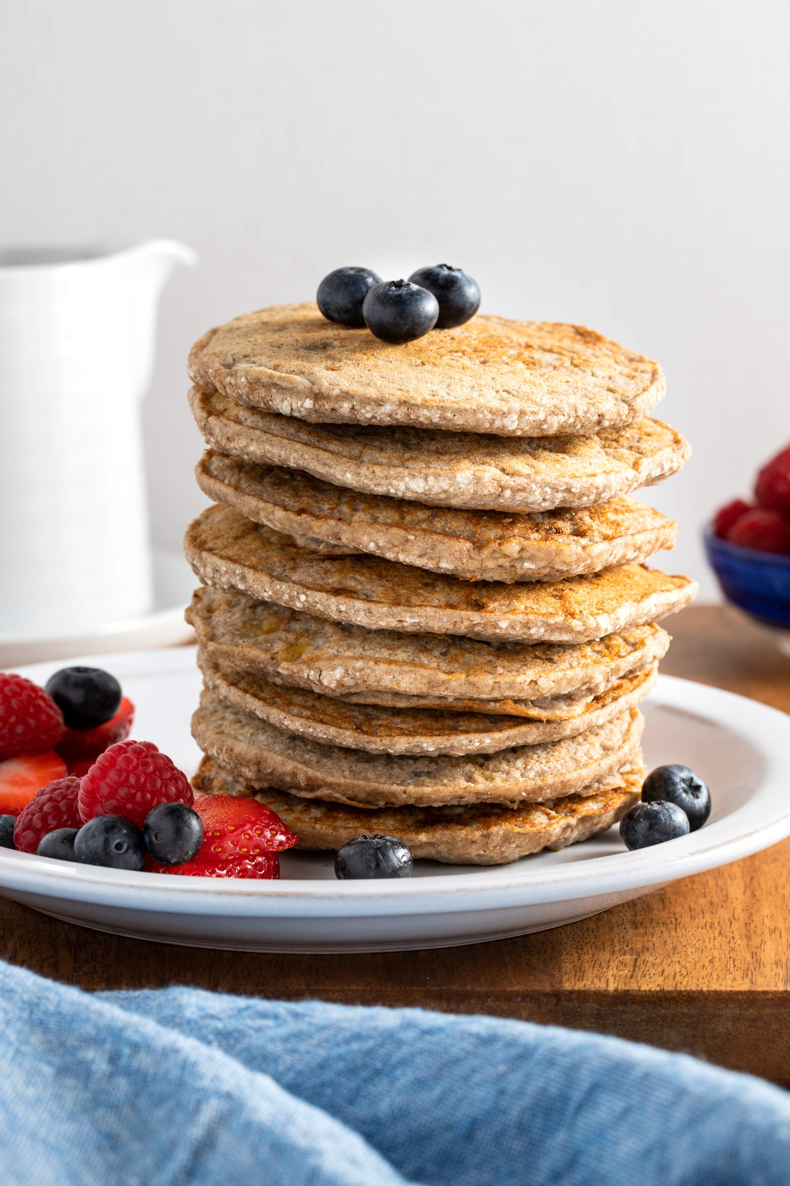 Stack of buckwheat banana pancakes with fresh fruit.